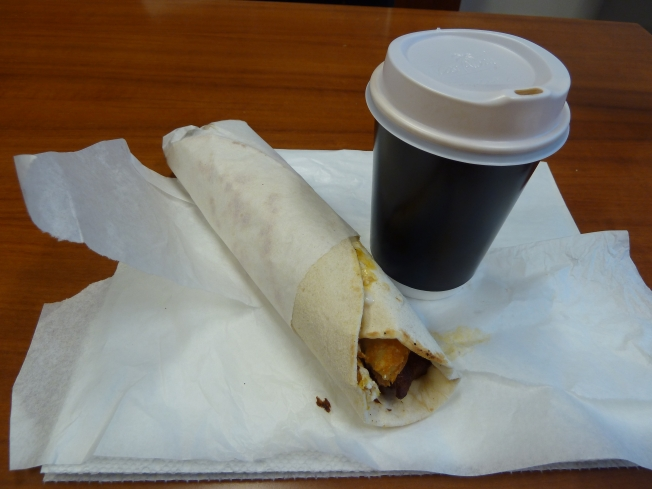 This is a Mavi Breakfast wrap which contains bacon, egg, mushrooms, cheese and a hashed brown. One of the best breakfasts on a work day.