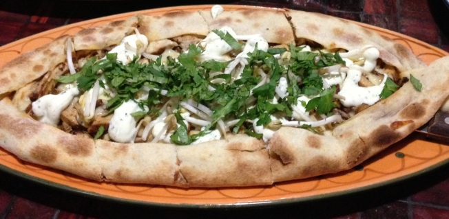Spit roasted lamb pizza garnished with rocket, minted yoghurt and sumac