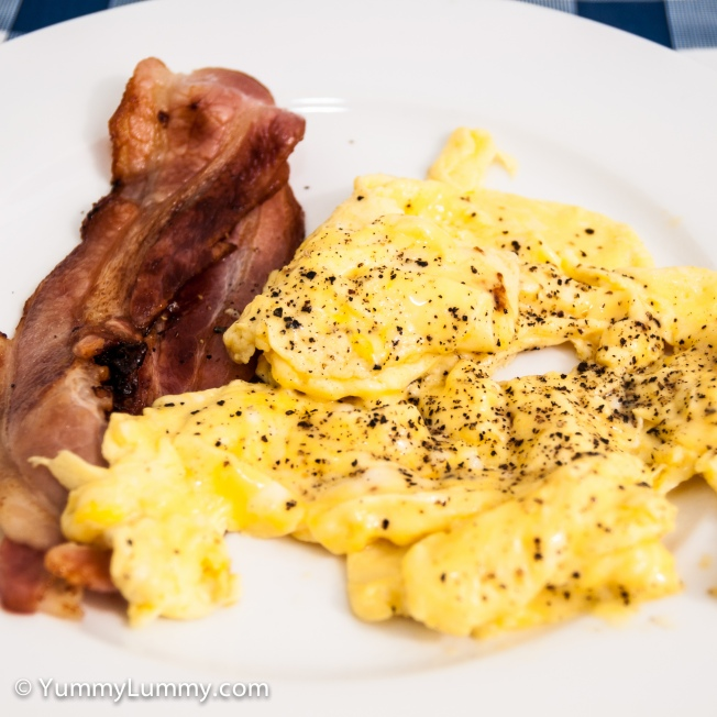 Creamy scrambled eggs made with bacon fat from crispy streaky bacon.
