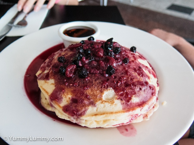 Pancake stack with berries and maple syrup