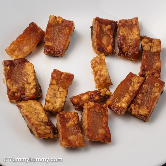 A snack of pork crackling while making a meal of pork rashers.